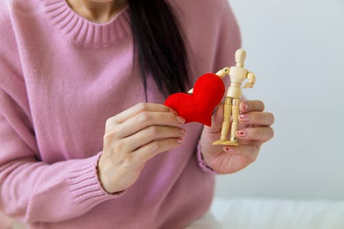 Crop woman with handmade heart and wooden figure