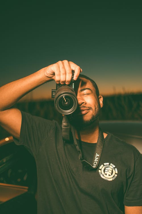 Crop cheerful African American male photographer standing in field at sunset time with photo camera covering half face in countryside