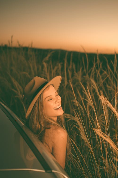 Happy woman in field at sunset