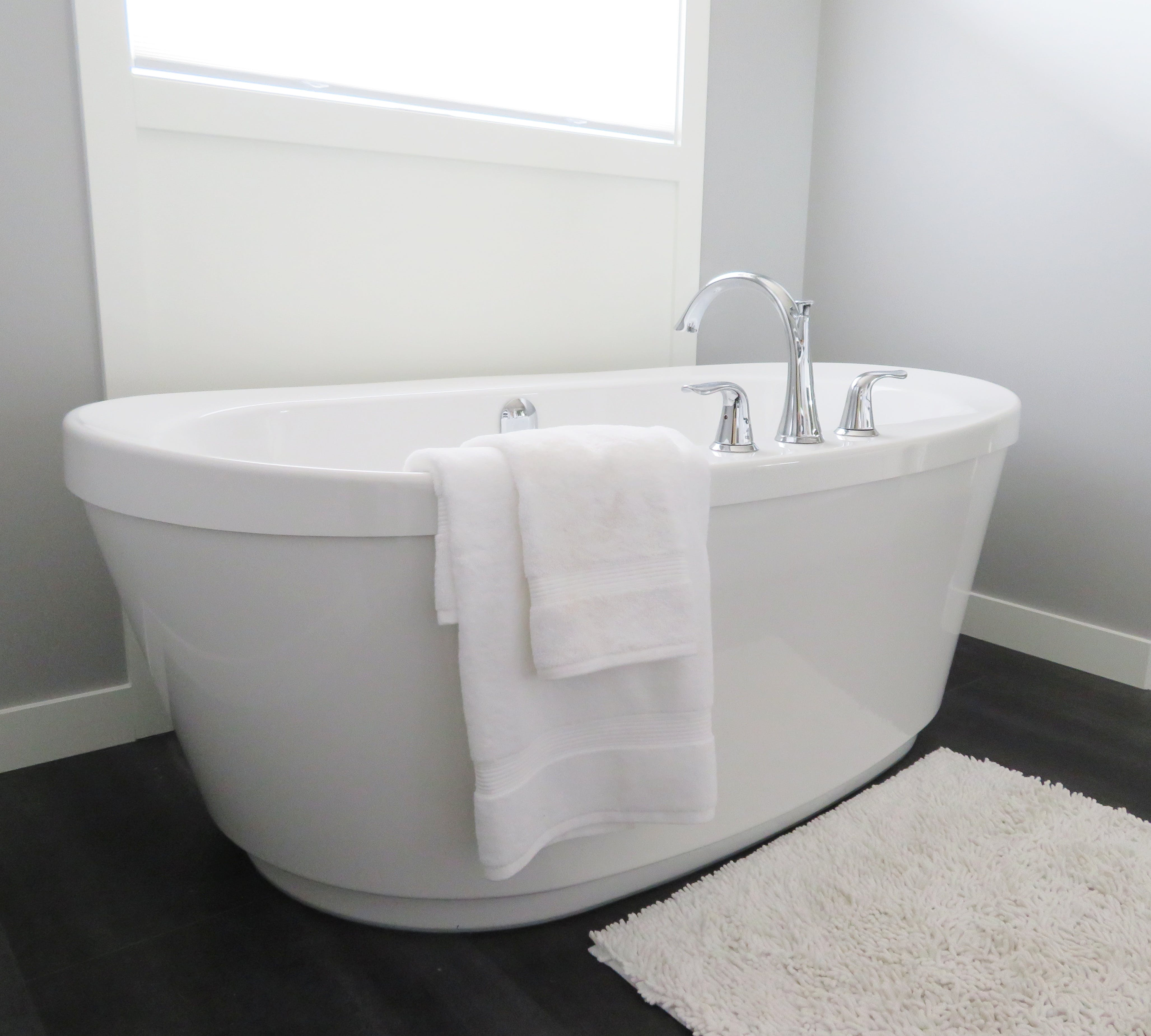 White Ceramic Bathtub Near Window