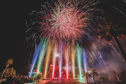 Long exposure of vibrant sparkling fireworks and bright multi colored Roman candles over palms and pavement at night