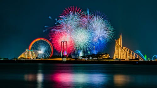 Bright fireworks in sky over amusement park and lake