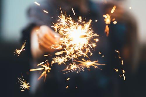 Faceless person holding bright sparkler