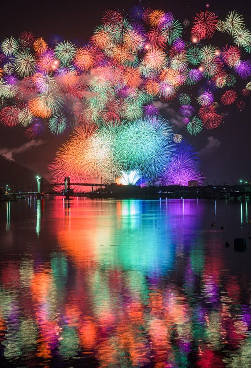 Vibrant fireworks reflecting from surface of lake