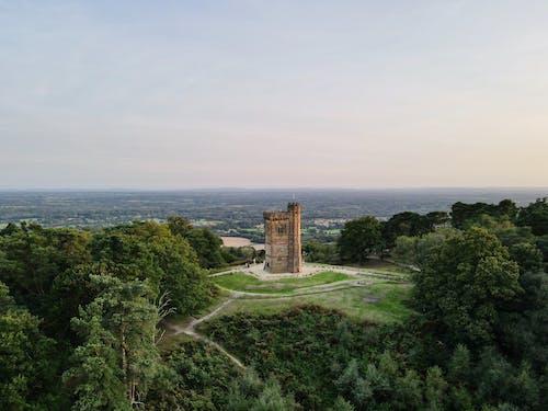 Gothic medieval tower on green hill under sundown sky