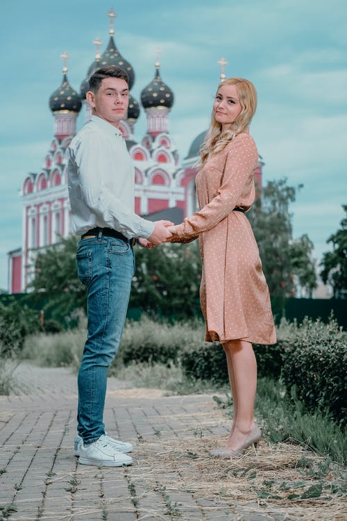 Side view full body young couple in smart casual clothes holding hands and looking at camera while standing against orthodox church on clear summer day