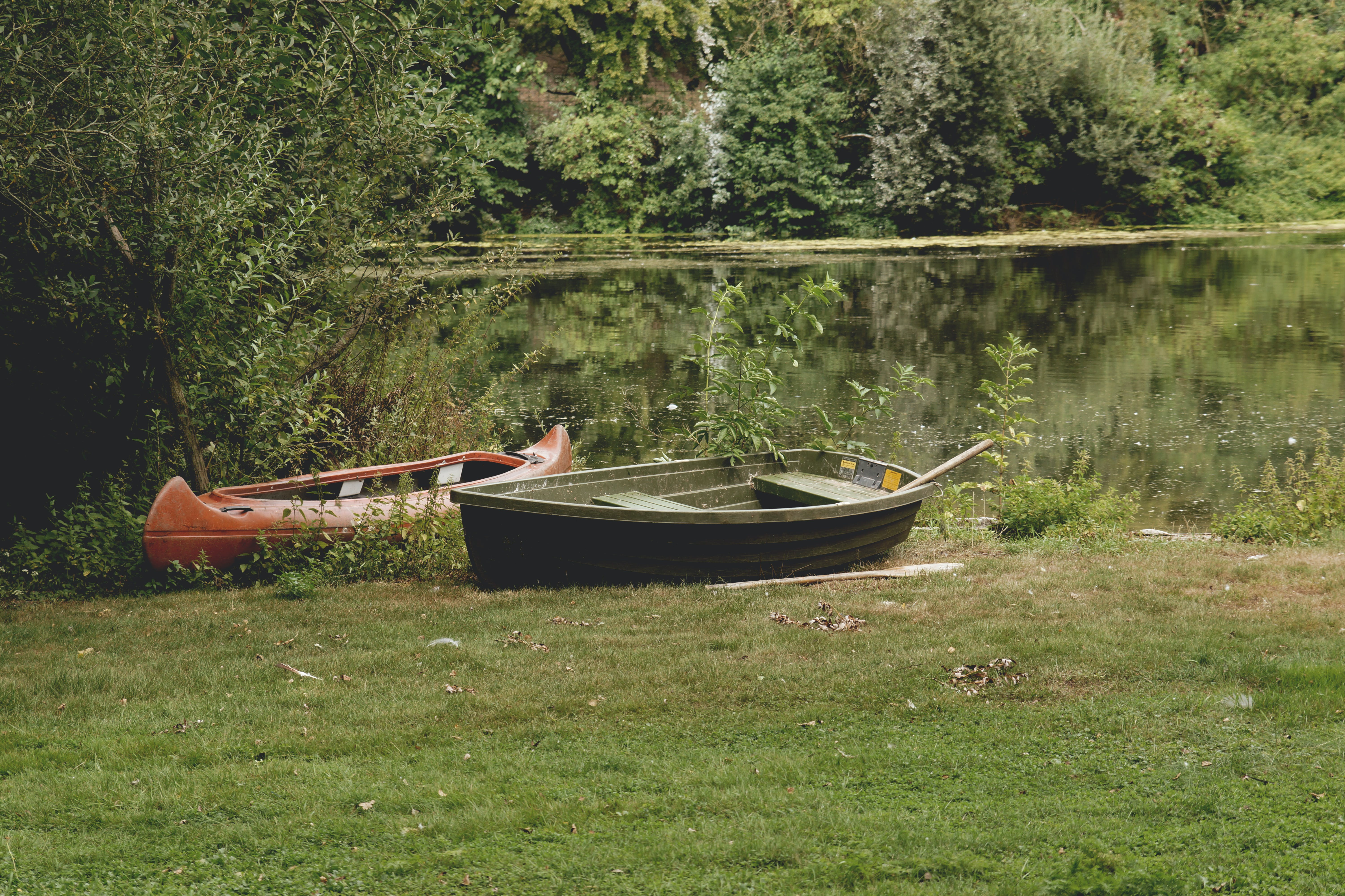 Two Black and Red Assorted-type Boats on Grass