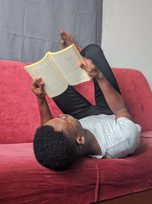 Man in Black Tank Top and Gray Pants Lying on Red Couch Reading Book