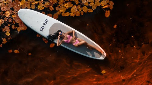 Woman in Pink Shirt Lying on White Surfboard on Brown Leaves