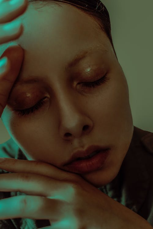 Headshot of attractive female with closed eyes and bright make up with hands near face in dim light in room