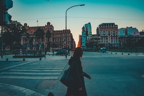 Woman in Black Coat Walking on Sidewalk