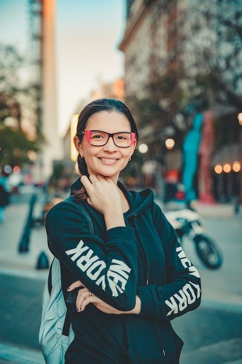 Woman in Blue and White Adidas Hoodie Wearing Black Framed Eyeglasses