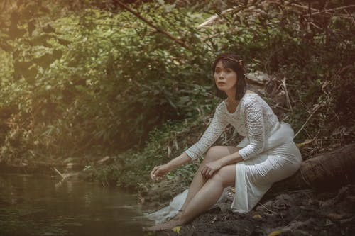 Full body of Asian female in white dress looking at camera while sitting on log near lake with feet in water