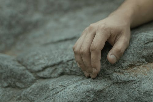 Selective focus of crop anonymous person touching stone surface at daytime