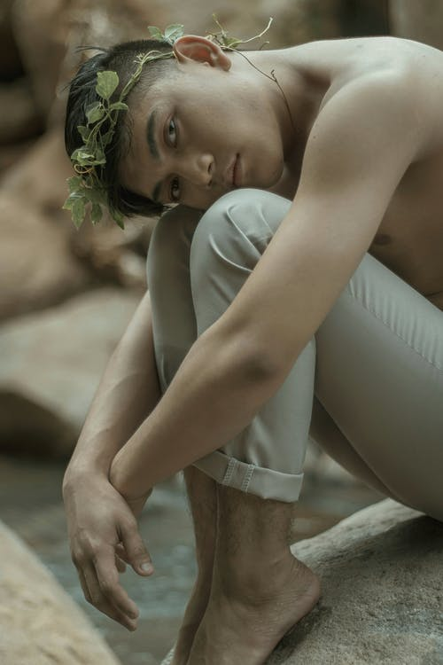 Barefooted melancholic Asian male embracing knees in nature