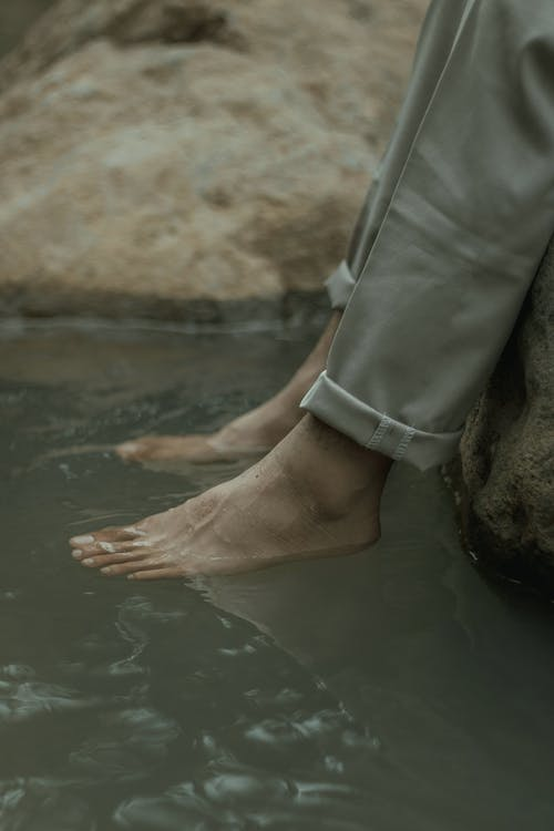 Unrecognizable person resting on river shore with feet in water
