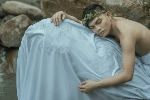 Young man as ancient Greek outfit resting on stones