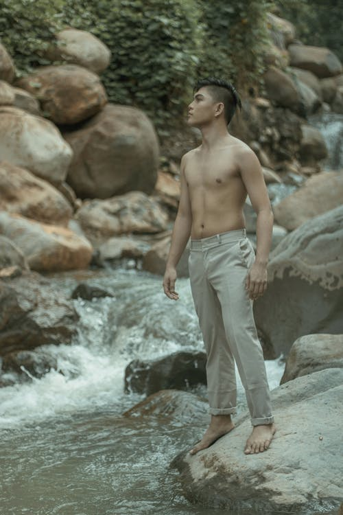Full body of young ethnic barefoot male looking away and standing on rough stone near swift stream