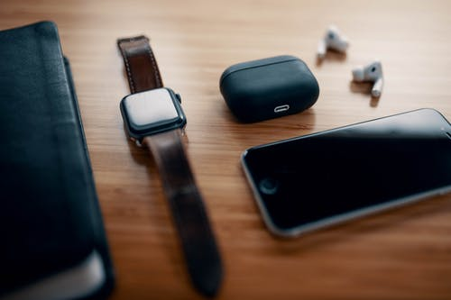 Black smart watch on leather strap and earbuds with charging case and smartphone near black notebook on wooden table