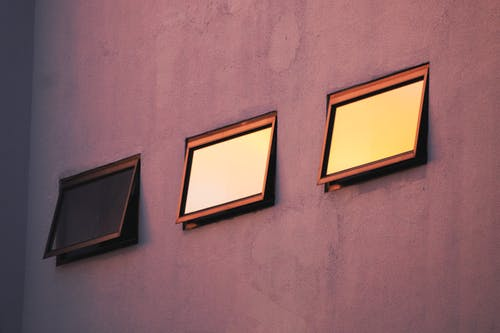 3 Brown Wooden Framed Windows on Gray Concrete Wall