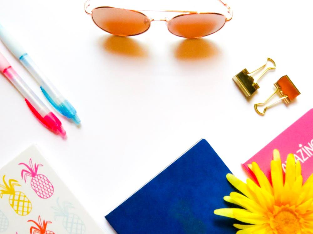 Brown Sunglasses Beside Click Pens