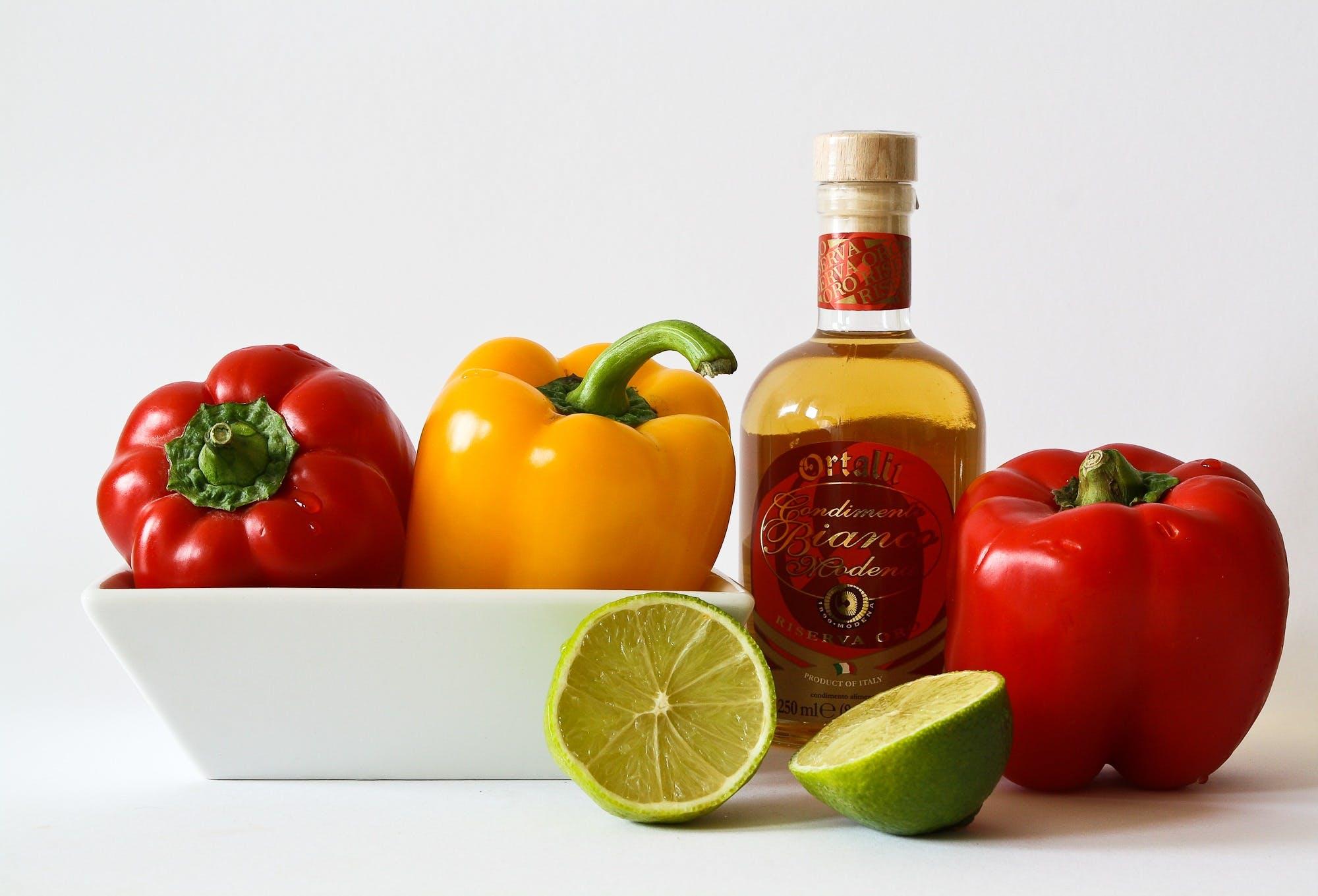 Red and Green Bell Pepper Inside White Ceramic Tray Near to Bottle and Lemon