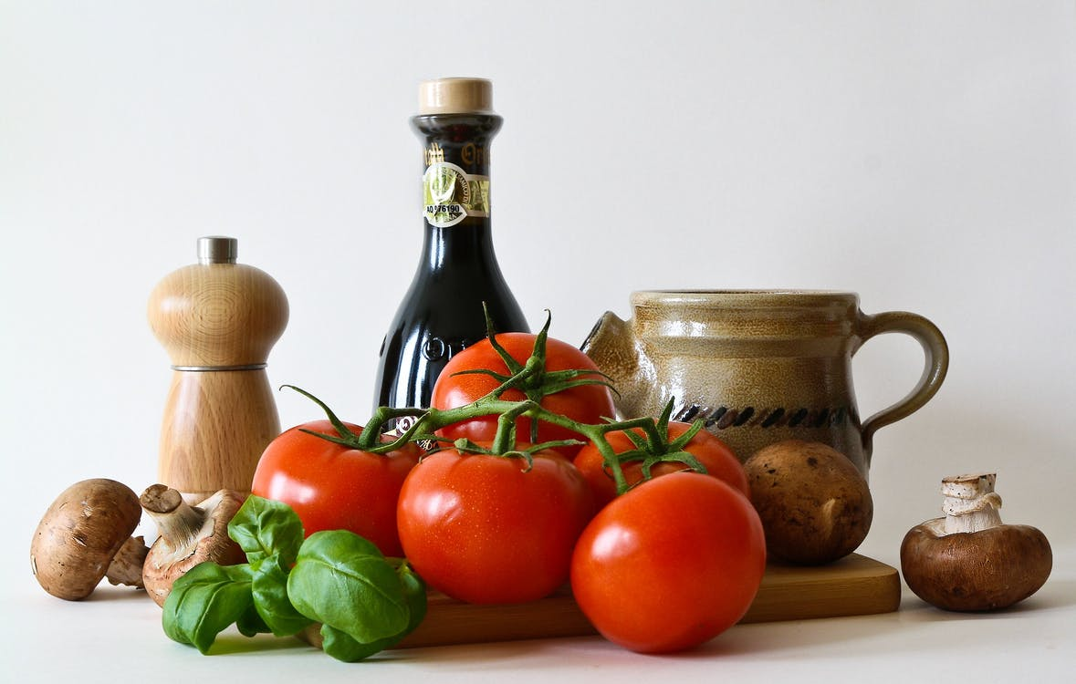 Red Tomatoes, Brown Mushrooms, Brown Bottle, and Chopping Board on White Surface