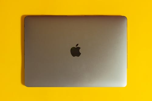 Gold Macbook on Yellow Table  A Gold Laptop on Yellow Surface