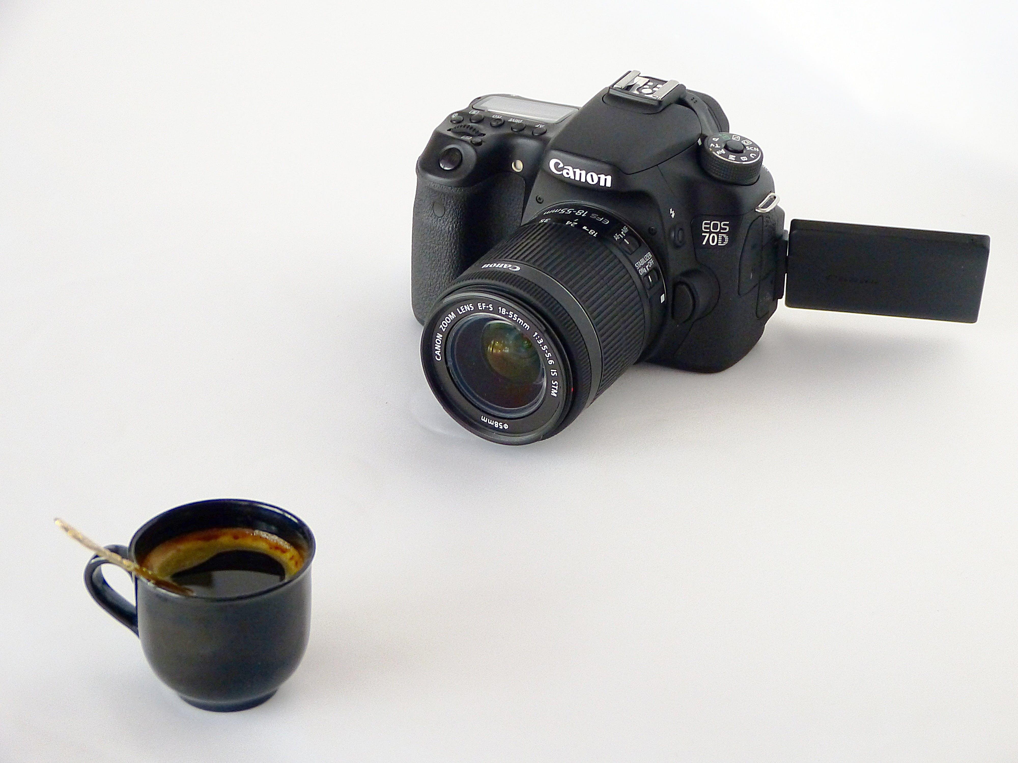 Black Canon Dslr Camera in Front of Coffee in Black Ceramic Teacup