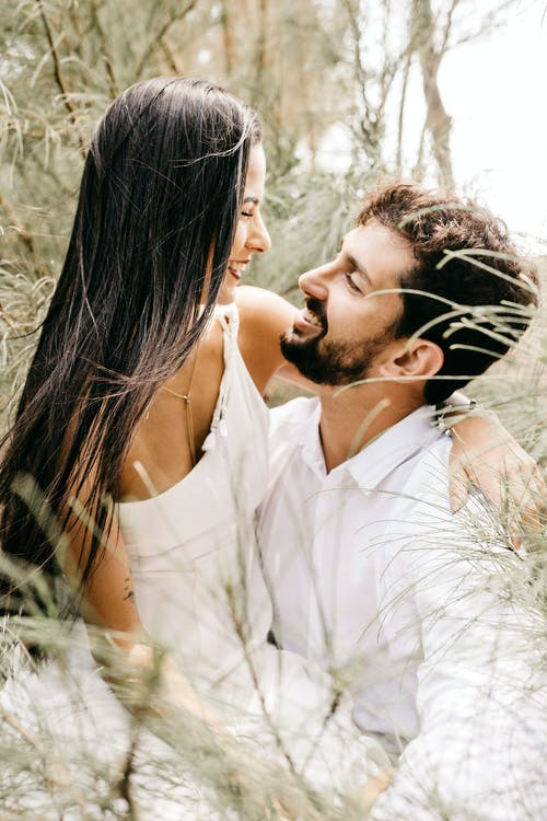 Bearded man with young cheerful woman smiling and hugging white wearing in branches in blurred landscape