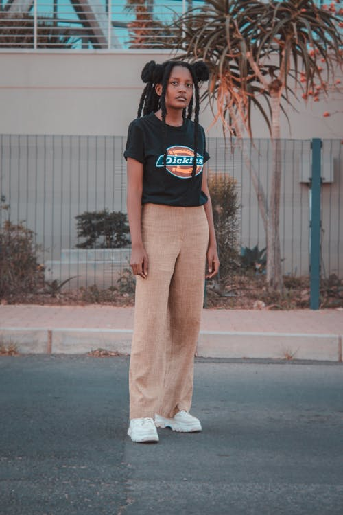 Woman in Black Crew Neck T-shirt and White Pants Standing on Gray Concrete Floor during
