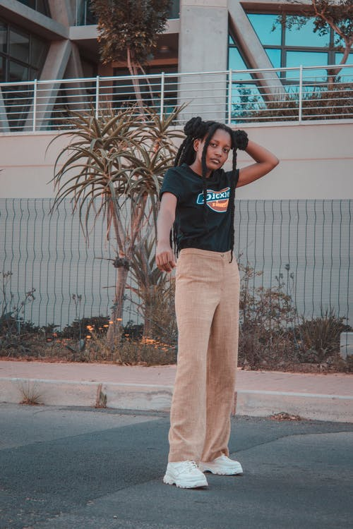 Woman in Black T-shirt and Brown Pants Standing on Sidewalk