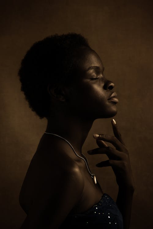 Young black woman with closed eyes touching chin