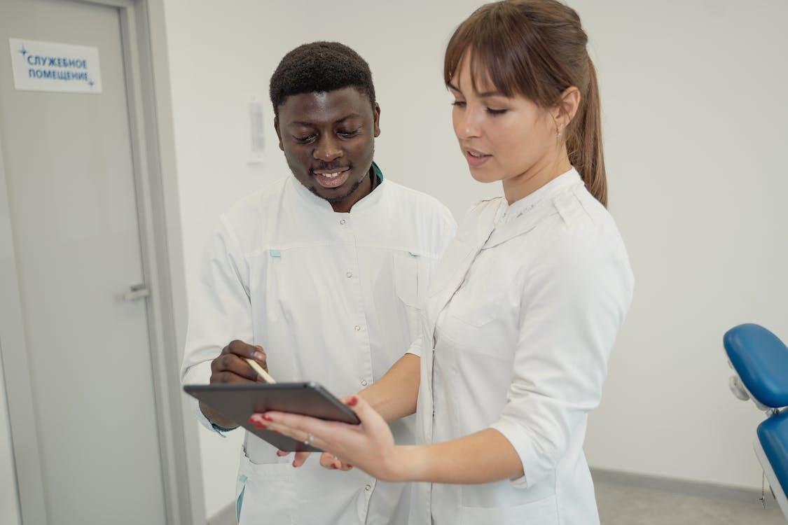 Man in White Dress Shirt Holding Black Tablet Computer Beside Woman in White Dress Shirt