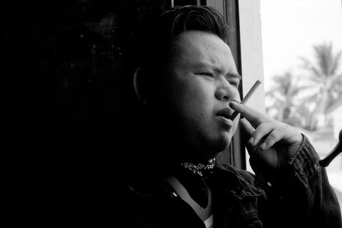 Black and white of pensive plus size ethnic male in casual clothes smoking cigarette and looking away in daytime