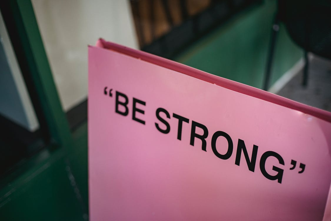 From above of pink signboard with black motivational phrase Be strong on street near green facade of building in city with blurred background