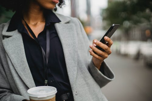 Unrecognizable ethnic female in formal clothes browsing cellphone while standing in city on blurred street with cup of drink during break