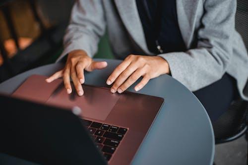Crop ethnic woman browsing laptop