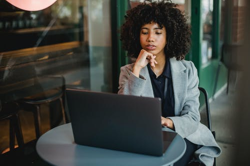 Concentrated African American female sitting at table in outdoor cafeteria and leaning on hand while browsing computer during online work