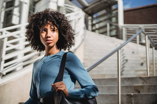 Young contemplative black female in casual wear with Afro hairstyle looking away near street staircase