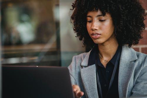 Crop black freelancer working on laptop in daytime