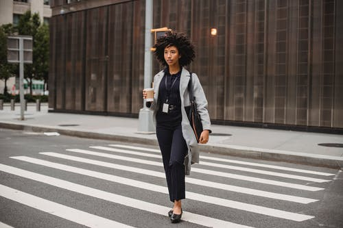 Stylish black office worker with takeaway coffee strolling on crosswalk