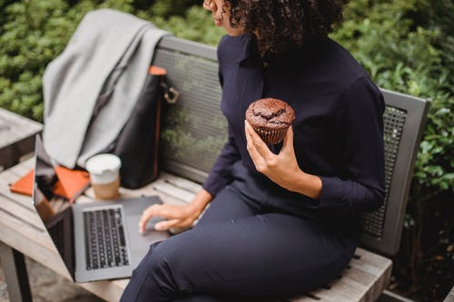 High angle of crop ethnic female distance worker browsing internet on netbook while sitting on street bench with tasty muffin