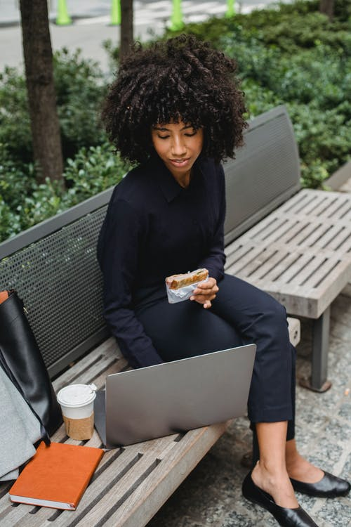 Black businesswoman with puff working on laptop on street bench