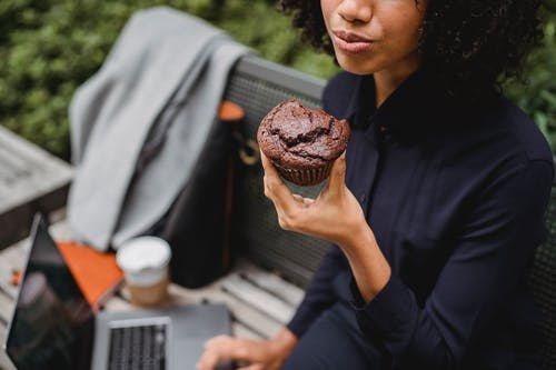 Crop black remote employee with tasty muffin and laptop outdoors