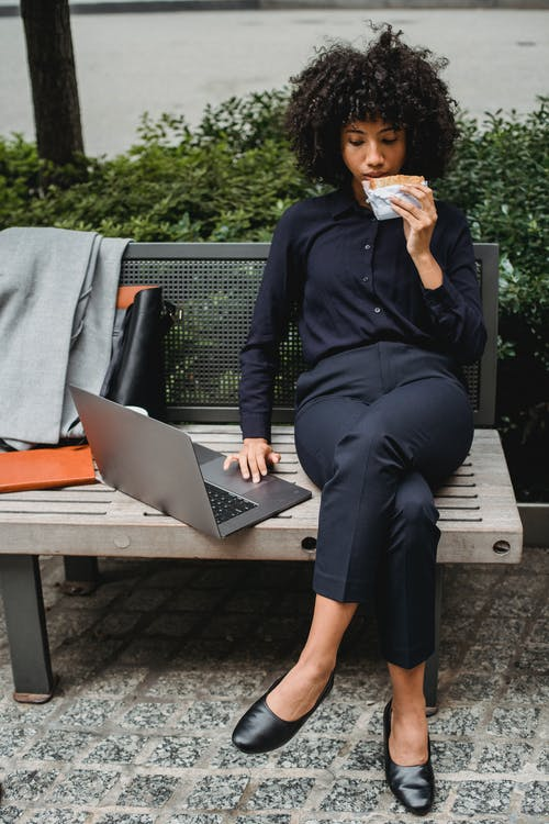 Busy African American woman in formal clothes sitting on bench and browsing netbook while having lunch in park