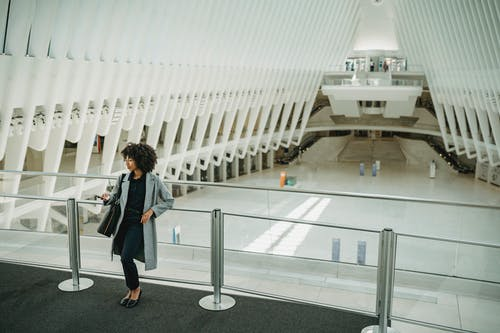 Woman in Black Jacket Standing Near White Concrete Building