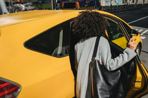 Unrecognizable woman getting in taxi on street