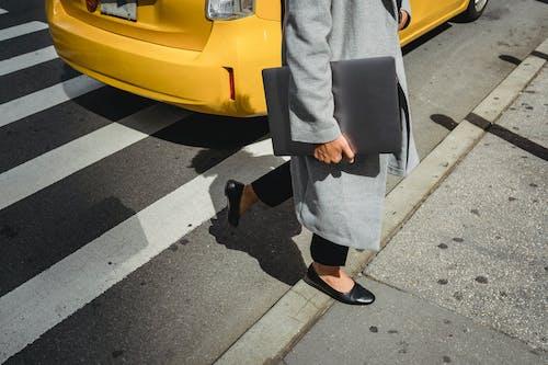 Crop woman crossing road against cab
