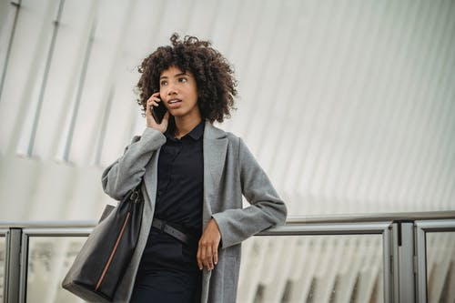 Stylish African American female with curly hair leaning on glass railing while having phone conversation and looking away